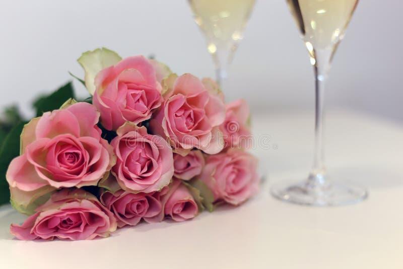 Δύο ποτήρια της σαμπάνιας και μιας ανθοδέσμης φιαγμένης από όμορφο ανοικτό κόκκινο/κοκκινίζουν ρόδινα τριαντάφυλλα στοκ φωτογραφίες με δικαίωμα ελεύθερης χρήσης