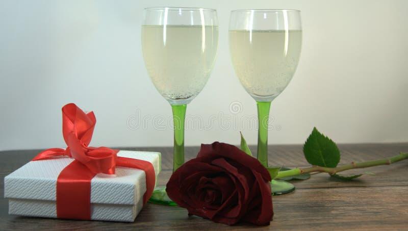 Δύο ποτήρια της σαμπάνιας, κόκκινα αυξήθηκαν και του κιβωτίου δώρων σε έναν ξύλινο πίνακα στοκ φωτογραφία με δικαίωμα ελεύθερης χρήσης