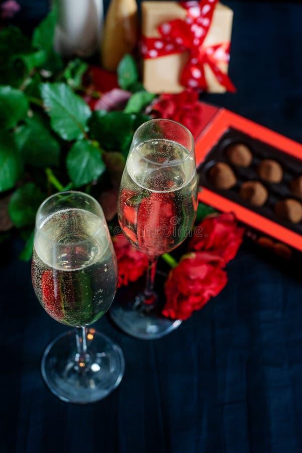 Δύο ποτήρια της σαμπάνιας, κόκκινες τριαντάφυλλα και καραμέλες σε ένα μαύρο υπόβαθρο στοκ φωτογραφία με δικαίωμα ελεύθερης χρήσης