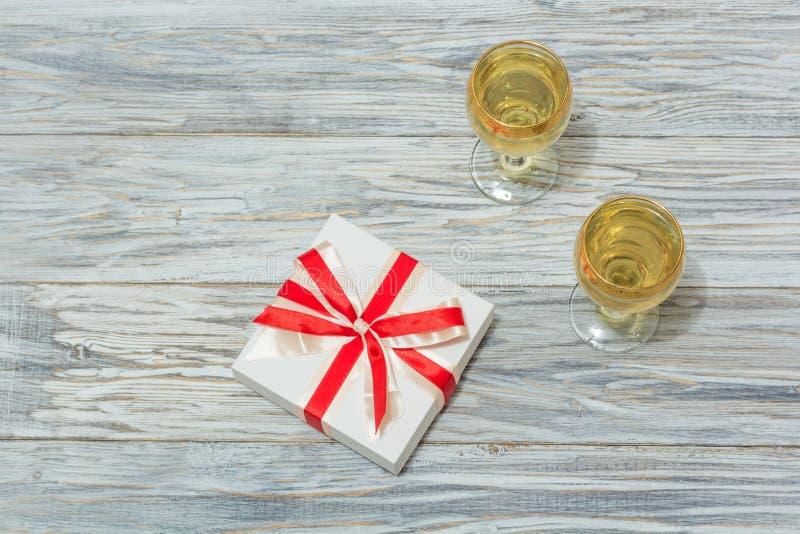 Δύο ποτήρια του άσπρου κρασιού και ενός δώρου στοκ φωτογραφία με δικαίωμα ελεύθερης χρήσης