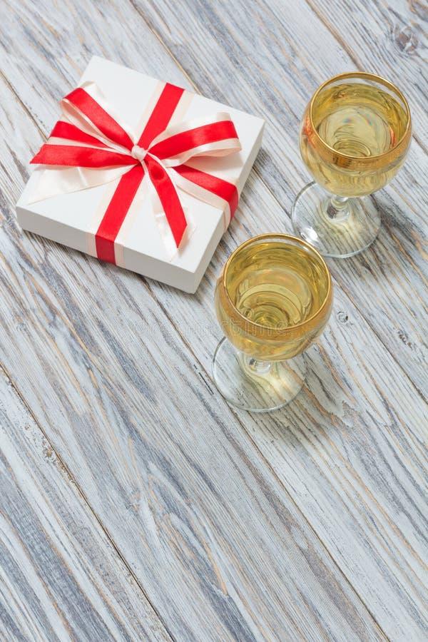 Δύο ποτήρια του άσπρου κρασιού και ενός δώρου στοκ εικόνες