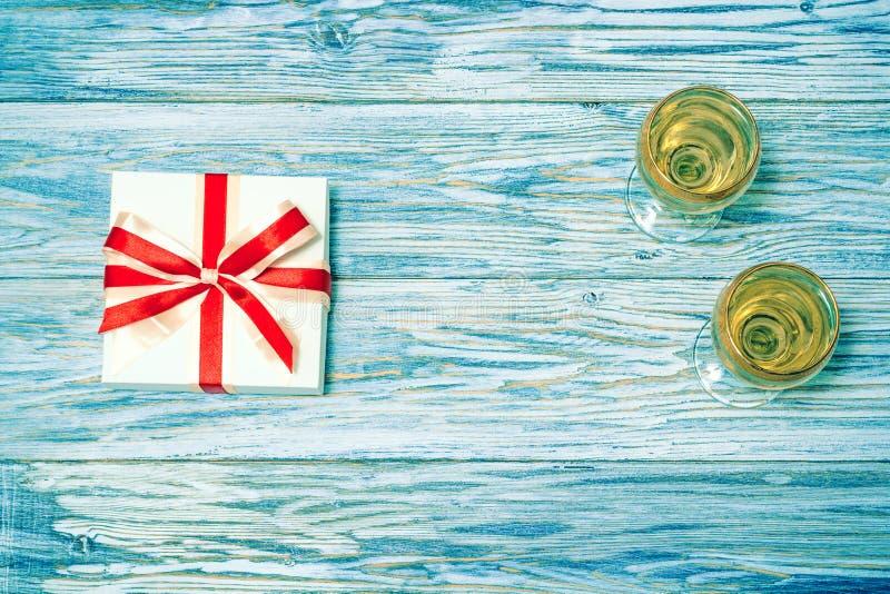 Δύο ποτήρια του άσπρου κρασιού και ενός δώρου στοκ εικόνα