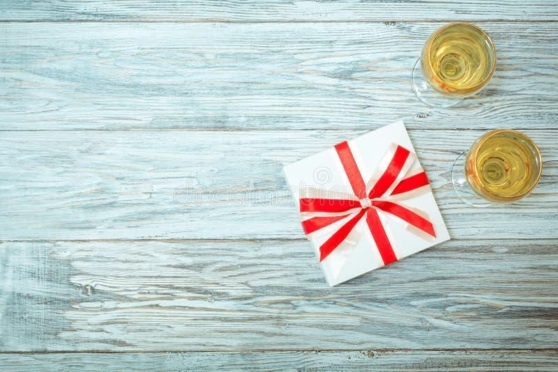 Δύο ποτήρια του άσπρου κρασιού και ενός δώρου στοκ εικόνα με δικαίωμα ελεύθερης χρήσης