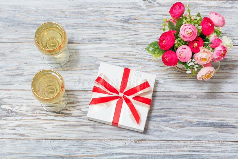 Δύο ποτήρια του άσπρου κρασιού, των λουλουδιών και ενός δώρου στοκ φωτογραφίες με δικαίωμα ελεύθερης χρήσης