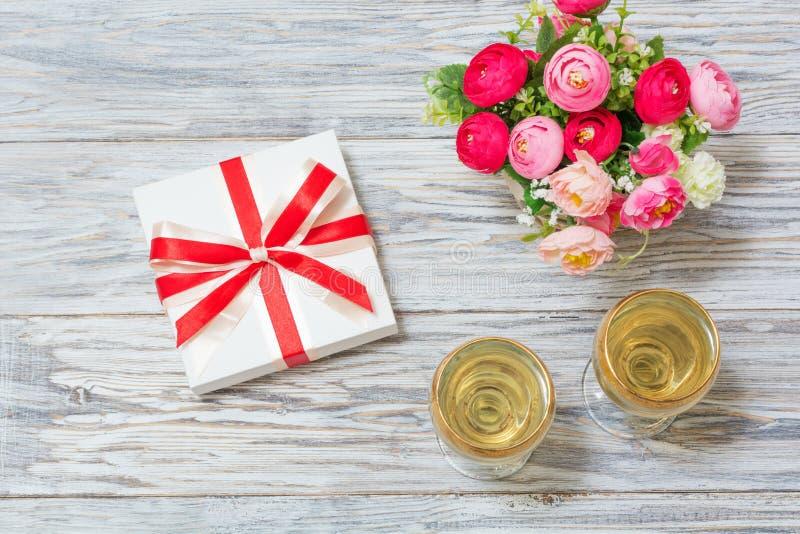 Δύο ποτήρια του άσπρου κρασιού, των λουλουδιών και ενός δώρου στοκ εικόνες