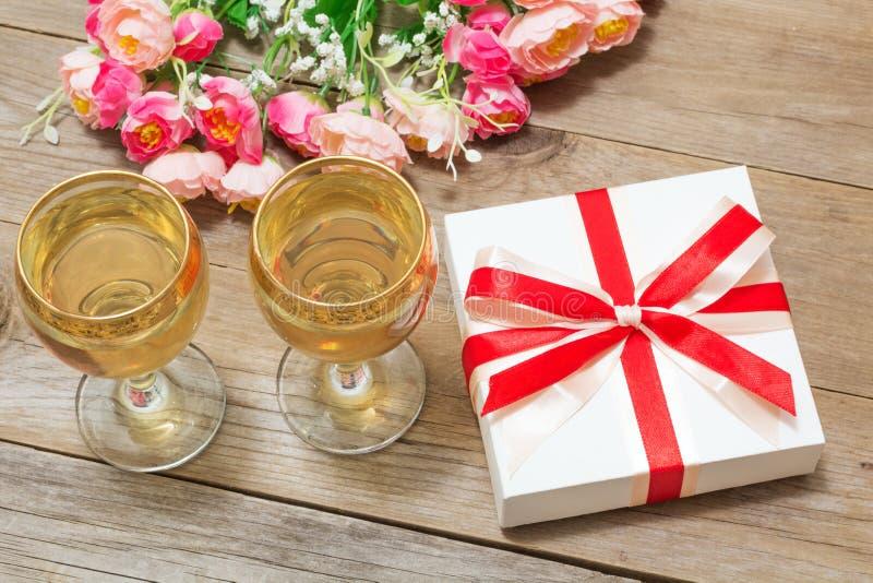 Δύο ποτήρια του άσπρου κρασιού, των λουλουδιών και ενός δώρου στοκ φωτογραφία με δικαίωμα ελεύθερης χρήσης