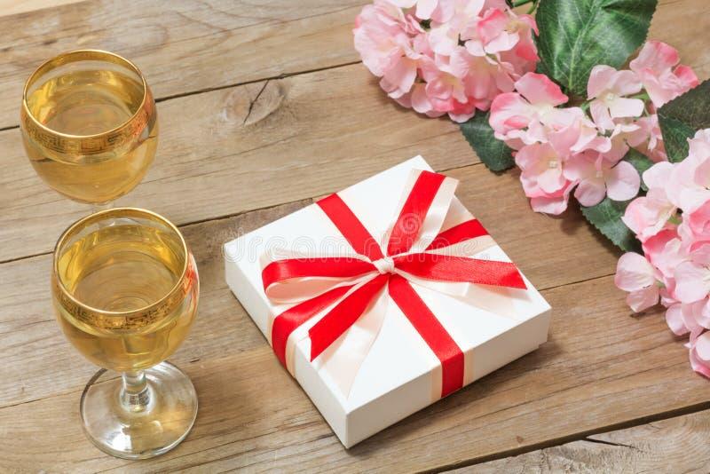 Δύο ποτήρια του άσπρου κρασιού, των λουλουδιών και ενός δώρου στοκ εικόνα