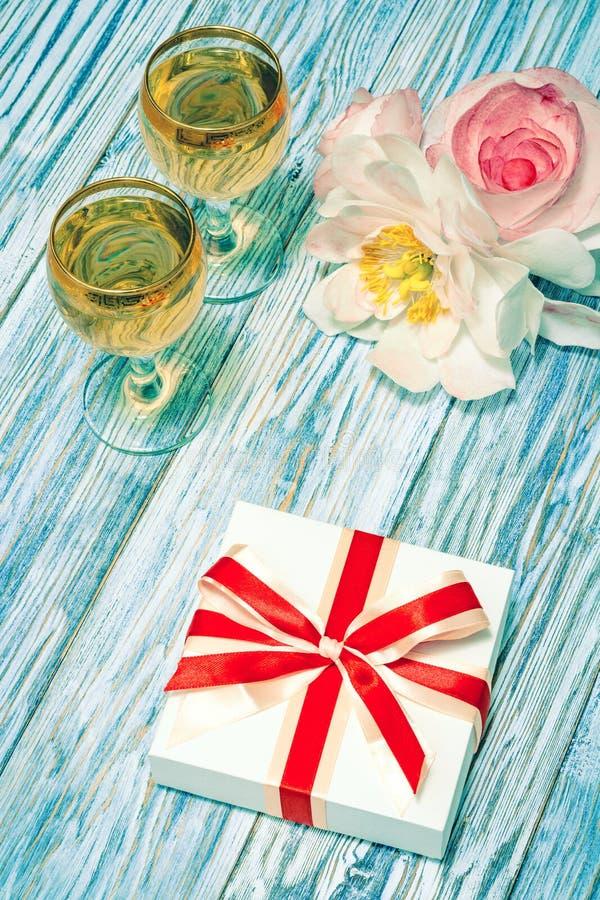 Δύο ποτήρια του άσπρου κρασιού, των λουλουδιών και ενός δώρου στοκ φωτογραφίες