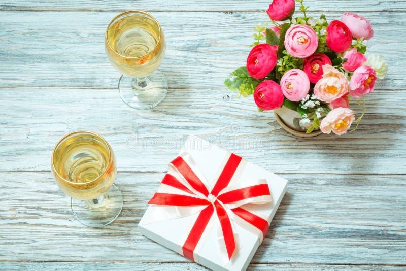 Δύο ποτήρια του άσπρου κρασιού, των λουλουδιών και ενός δώρου στοκ φωτογραφία
