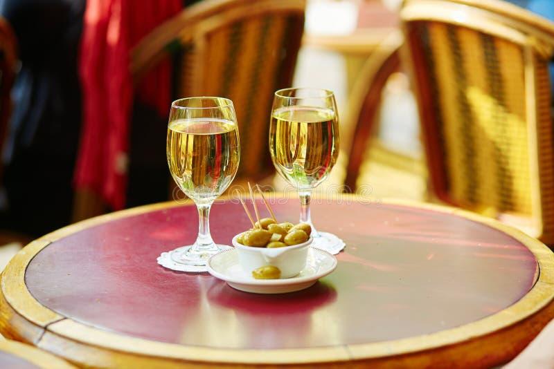 Δύο ποτήρια του άσπρων κρασιού και των ελιών στοκ εικόνες
