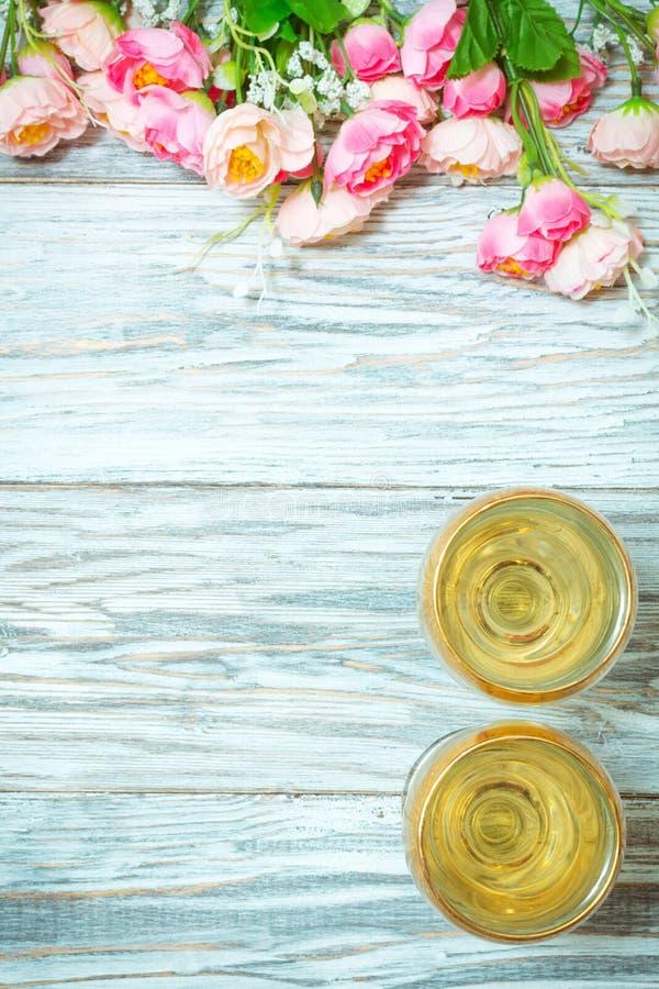 Δύο ποτήρια του άσπρων κρασιού και των λουλουδιών στοκ εικόνες