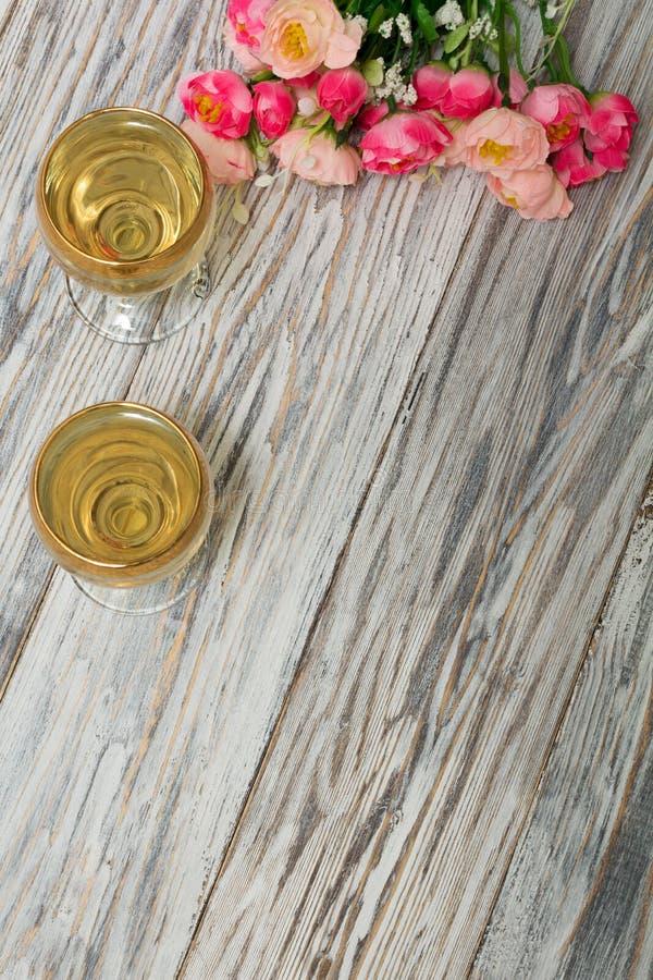 Δύο ποτήρια του άσπρων κρασιού και των λουλουδιών στοκ εικόνα