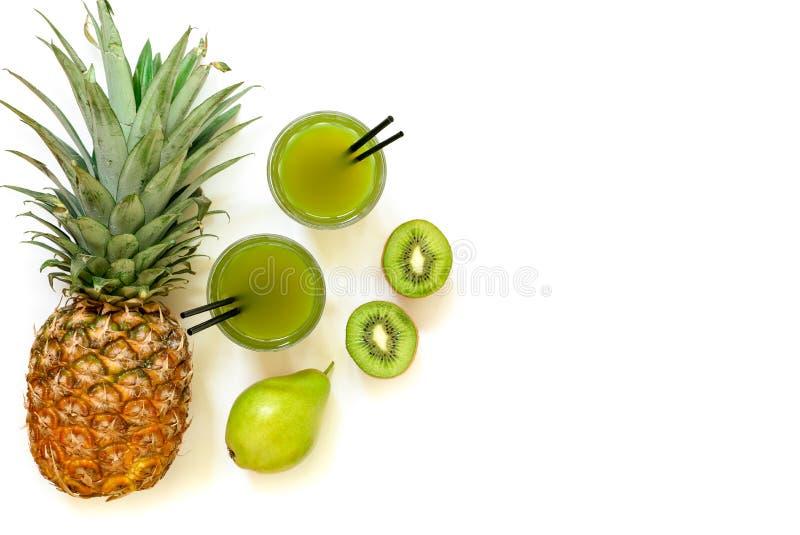 Δύο ποτήρια του ακτινίδιου, του ανανά, του χυμού αχλαδιών που απομονώνονται στο λευκό και των συστατικών στοκ φωτογραφίες