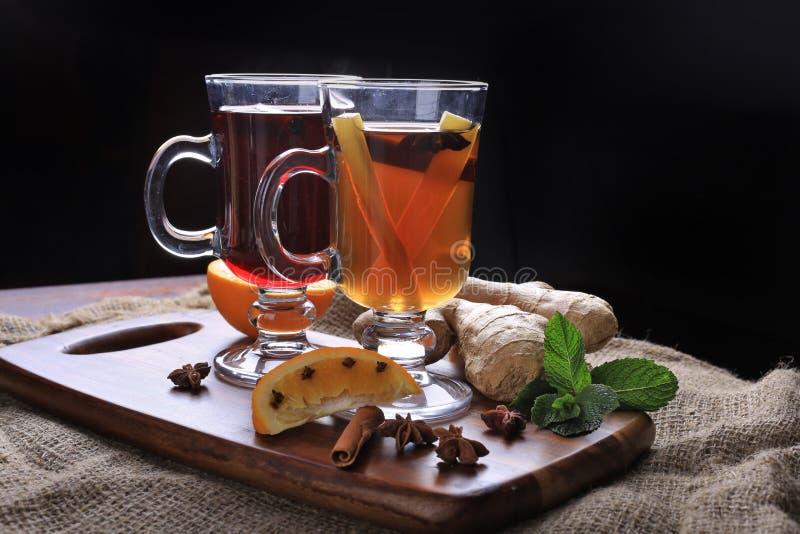 Δύο ποτήρια του καυτού θερμαμένου κρασιού με τα καρυκεύματα και της πιπερόριζας στο ξύλο στοκ εικόνες