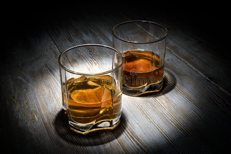 Δύο ποτήρια του ουίσκυ σε έναν εκλεκτής ποιότητας ξύλινο πίνακα σε ένα μαύρο υπόβαθρο στοκ εικόνα