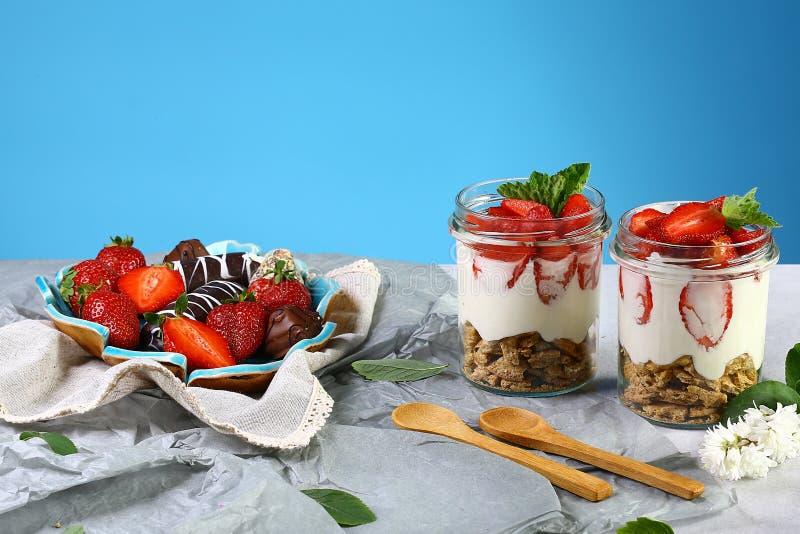 Δύο ποτήρια του υγιούς φρέσκου γιαουρτιού φραουλών με τα φρέσκα μούρα, oatmeal ξύλινο κουτάλι μπισκότων, marshmallow, σοκολάτα, ρ στοκ εικόνες