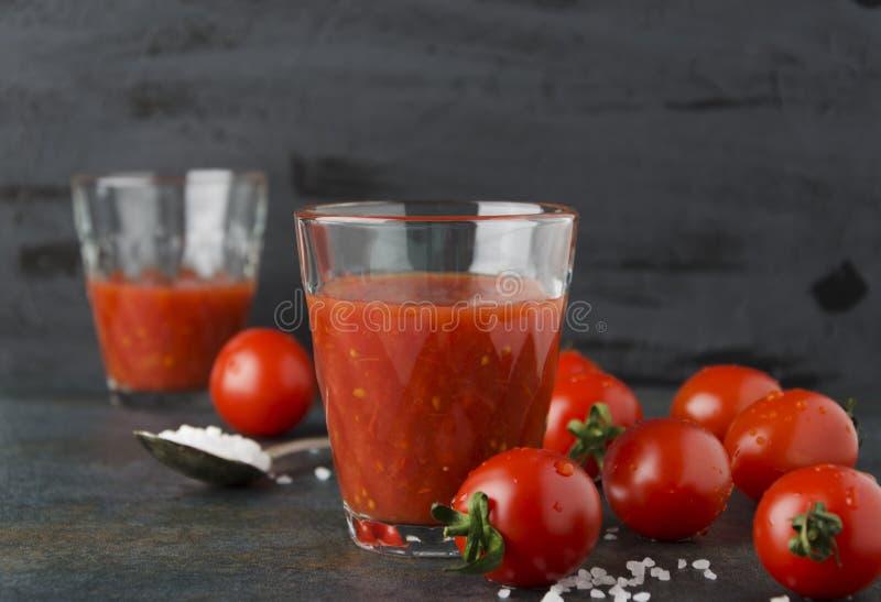 Δύο ποτήρια του φρέσκου χυμού ντοματών με το άλας, ντομάτες κερασιών στο σκοτεινό υπόβαθρο στοκ εικόνα με δικαίωμα ελεύθερης χρήσης