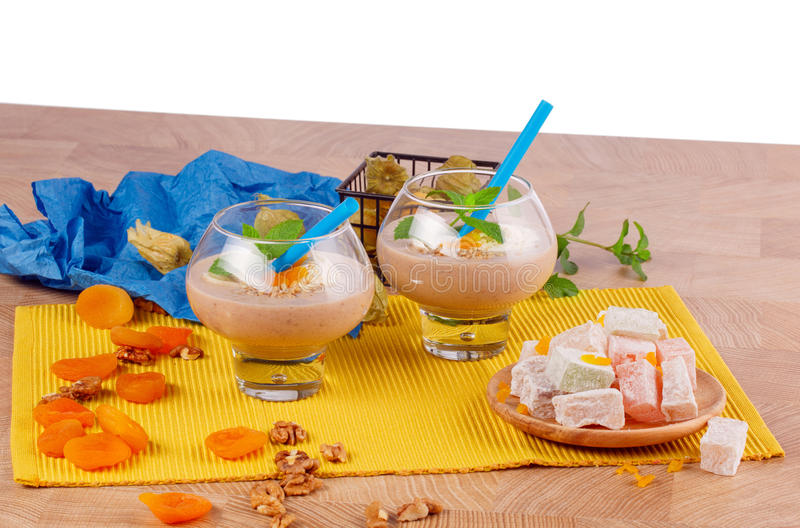 Δύο ποτήρια των κοκτέιλ με τα ξύλα καρυδιάς και ξηρά βερίκοκα, φύλλα της μέντας, rahat lokum, σε ένα άσπρο υπόβαθρο στοκ εικόνα