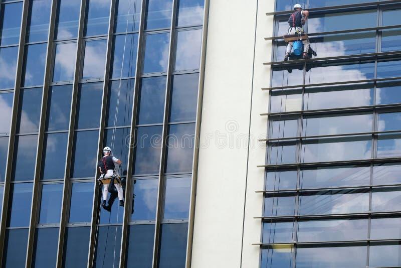 Δύο που αναρριχούνται στους εργαζομένους που καθαρίζουν τον εξωτερικό τοίχο γυαλιού ενός κτηρίου στοκ εικόνες με δικαίωμα ελεύθερης χρήσης