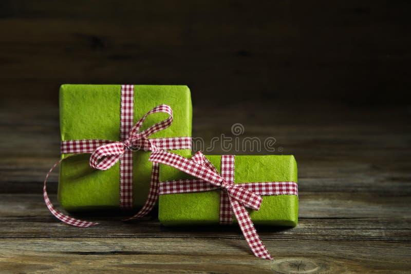 Δύο πράσινα δώρα με την κόκκινη άσπρη ελεγμένη κορδέλλα στο ξύλινο backgr στοκ φωτογραφία