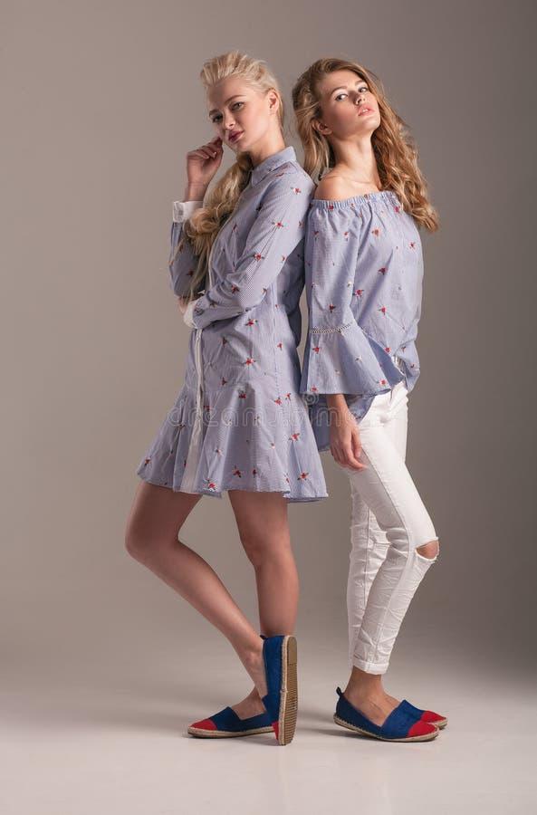 Δύο πρότυπα στο μπλε φόρεμα και την μπλούζα με τα τζιν που θέτουν στο γκρίζο BA στοκ φωτογραφία