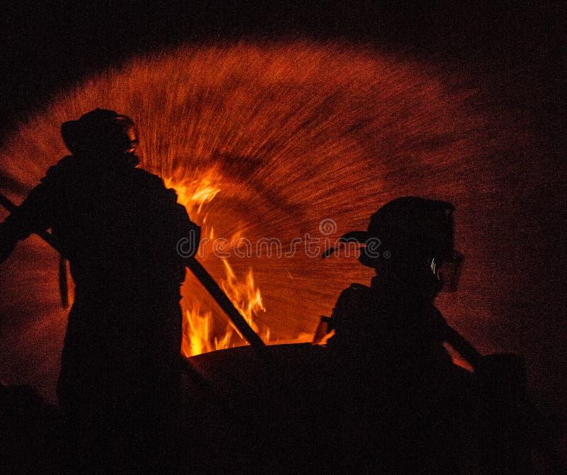 Δύο πυροσβέστες που επιτίθενται σε μια πυρκαγιά στοκ εικόνα με δικαίωμα ελεύθερης χρήσης