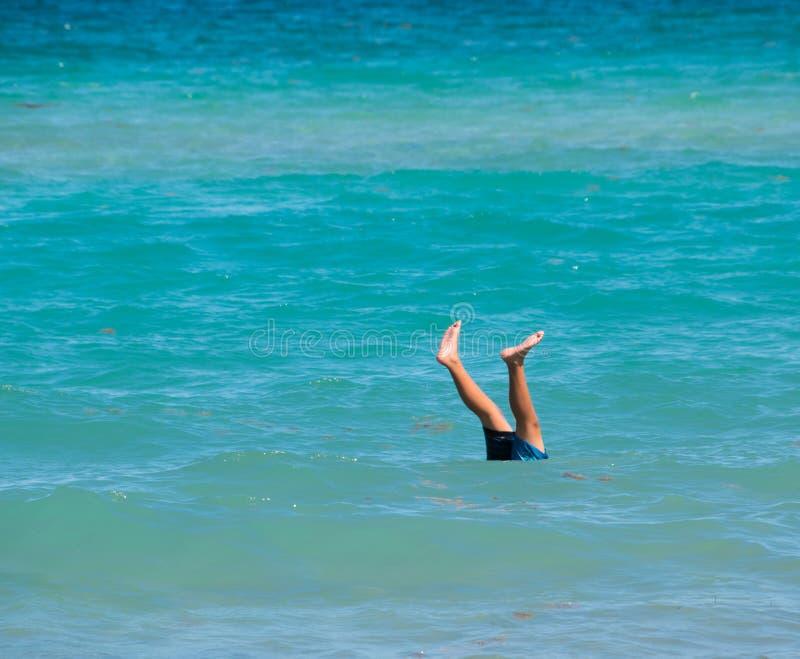Δύο πόδια που κολλούν επάνω από τον όμορφο μπλε ήρεμο ωκεανό στοκ εικόνα