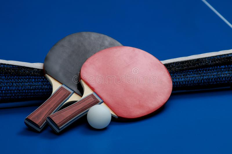 Δύο ρακέτες αντισφαίρισης Ρακέτες επιτραπέζιας αντισφαίρισης και μια σφαίρα σε έναν μπλε πίνακα αντισφαίρισης στοκ φωτογραφίες