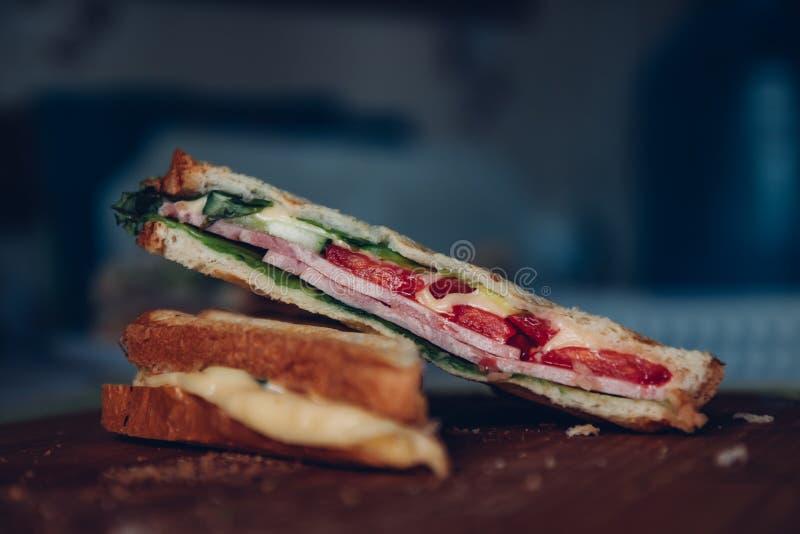 Δύο σάντουιτς σε ένα ξύλινο υπόβαθρο, τοπ άποψη Ο σωρός του panini με το ζαμπόν, το τυρί και το μαρούλι στριμώχνουν σε έναν τέμνο στοκ εικόνες