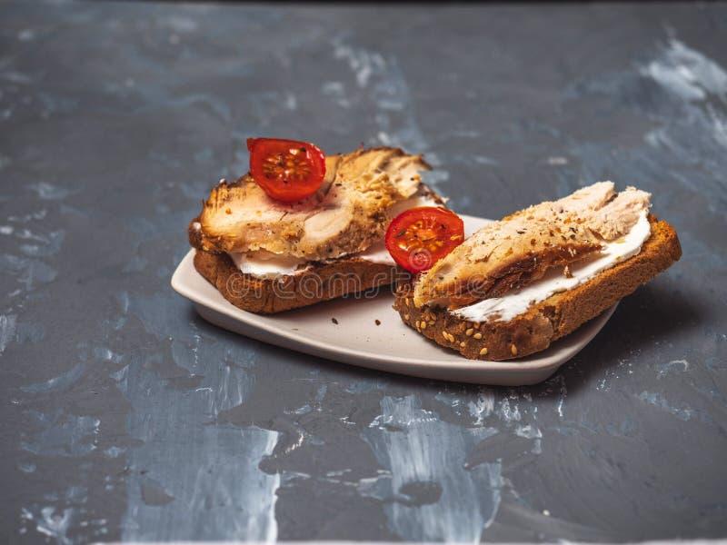 Δύο σάντουιτς της Τουρκίας με το ζαμπόν, το τυρί στάρπης και τις ντομάτες κερασιών σε ένα γκρίζο ξύλινο υπόβαθρο στοκ εικόνες με δικαίωμα ελεύθερης χρήσης