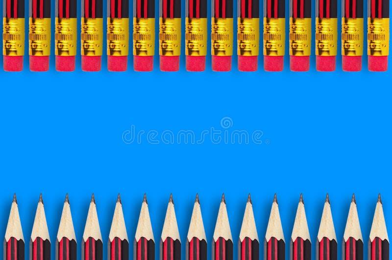 Δύο σειρές των νέων ξύλινων από γραφίτη μολυβιών με τη λαστιχένια άκρη γομών διασκόρπισαν στο μπλε υπόβαθρο στοκ εικόνα με δικαίωμα ελεύθερης χρήσης