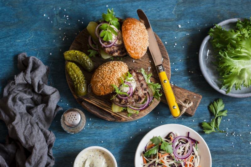 Δύο σπιτικά burgers σε έναν ξύλινο τέμνοντα πίνακα, τοπ άποψη στοκ φωτογραφία