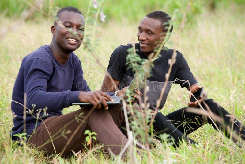 Δύο σπουδαστές εργάζονται μαζί στο lap-top στο πάρκο στοκ εικόνες με δικαίωμα ελεύθερης χρήσης