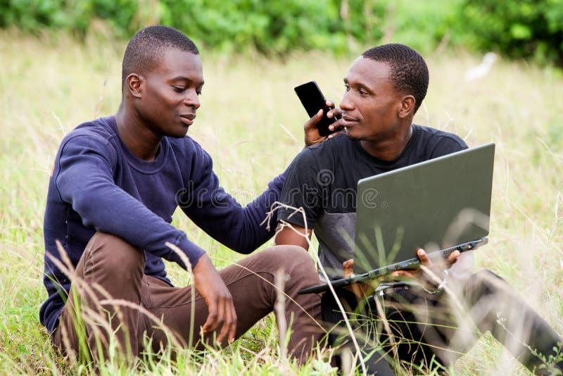Δύο σπουδαστές εργάζονται μαζί στο lap-top στο πάρκο στοκ φωτογραφίες