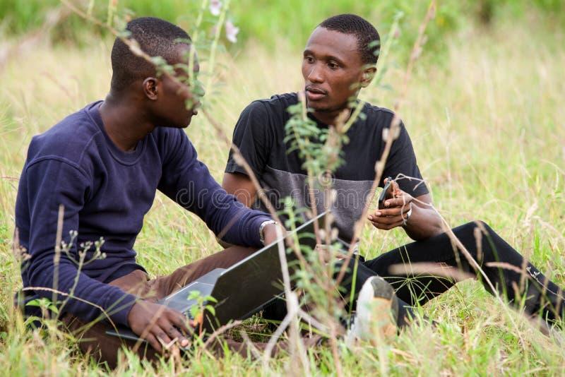 Δύο σπουδαστές εργάζονται μαζί στο lap-top στο πάρκο στοκ εικόνα με δικαίωμα ελεύθερης χρήσης