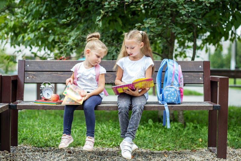 Δύο σπουδαστές που διαβάζονται τα βιβλία μετά από τις κατηγορίες Η έννοια του σχολείου, μελέτη, εκπαίδευση, φιλία, παιδική ηλικία στοκ φωτογραφία