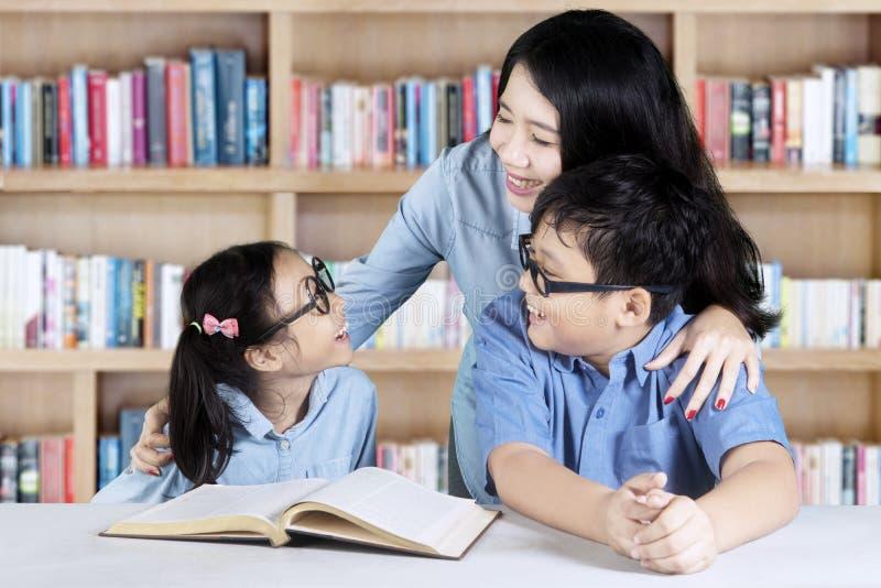 Δύο σπουδαστές που μιλούν με το δάσκαλό της στοκ φωτογραφία