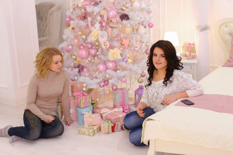 Δύο στενοί φίλοι μοιράζονται τις ευχάριστες συγκινήσεις και τα εορταστικά δώρα, κάθονται στοκ εικόνα