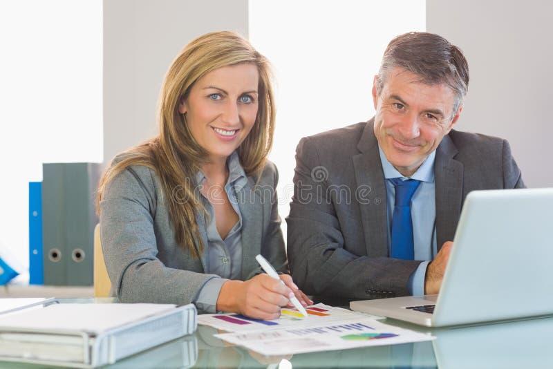 Δύο συγκεντρωμένοι επιχειρηματίες που χαμογελούν στη κάμερα που προσπαθεί να καταλάβει τους αριθμούς στοκ εικόνες με δικαίωμα ελεύθερης χρήσης