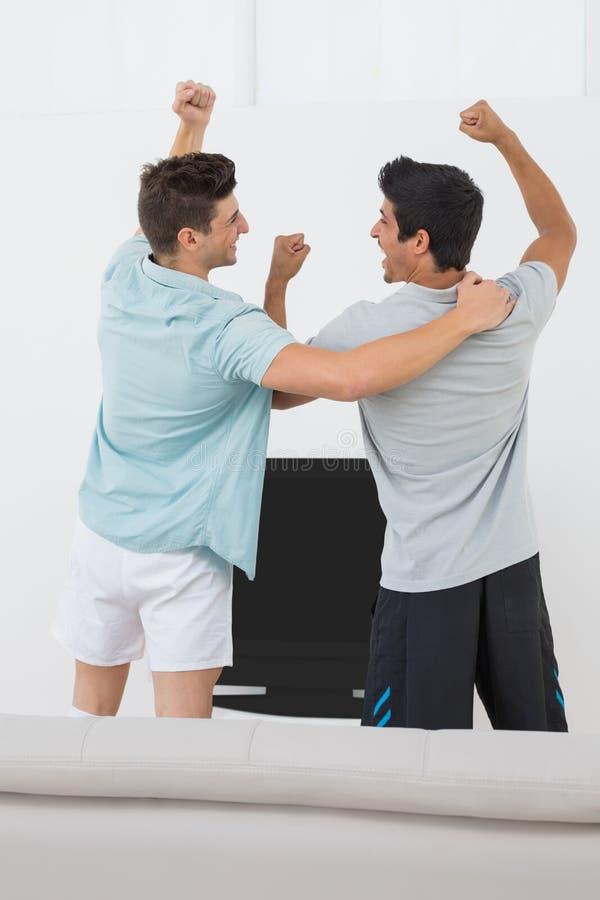 Δύο συγκινημένοι ανεμιστήρες ποδοσφαίρου που προσέχουν τη TV στοκ εικόνα