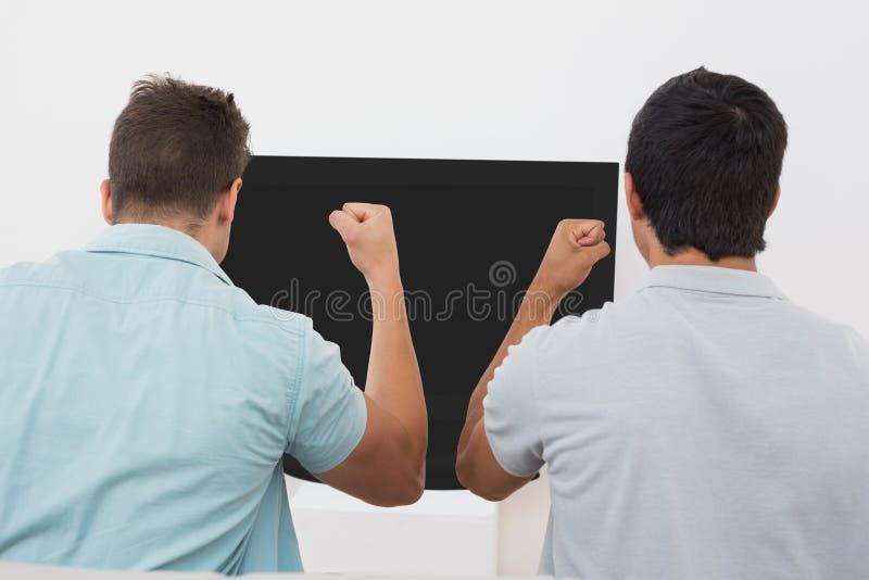 Δύο συγκινημένοι ανεμιστήρες ποδοσφαίρου που προσέχουν τη TV στοκ εικόνες