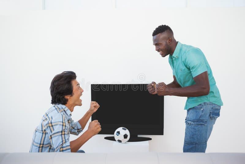 Δύο συγκινημένοι ανεμιστήρες ποδοσφαίρου που προσέχουν τη TV στοκ φωτογραφία