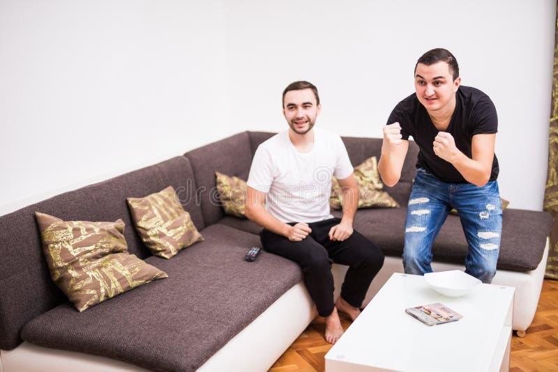 Δύο συγκινημένοι θαυμαστές ποδοσφαίρου κάθονται στον καναπέ και στόχο ομάδων προσοχής τον αγαπημένο στη TV στοκ φωτογραφίες