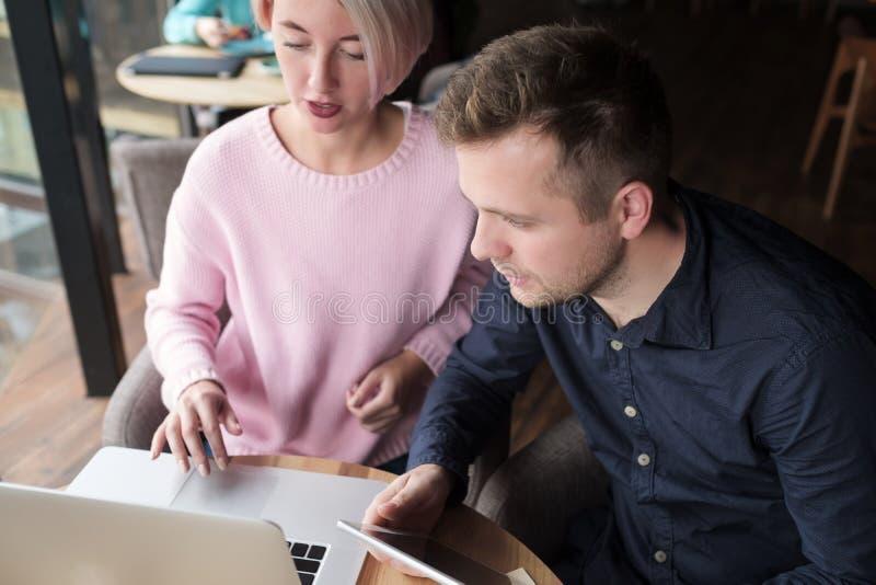 Δύο συνάδελφοι που εργάζονται μαζί στο lap-top Αρκετά πεπειραμένη γυναίκα που εξηγεί την κατώτερη πώς να χρησιμοποιήσει τον υπολο στοκ εικόνες με δικαίωμα ελεύθερης χρήσης
