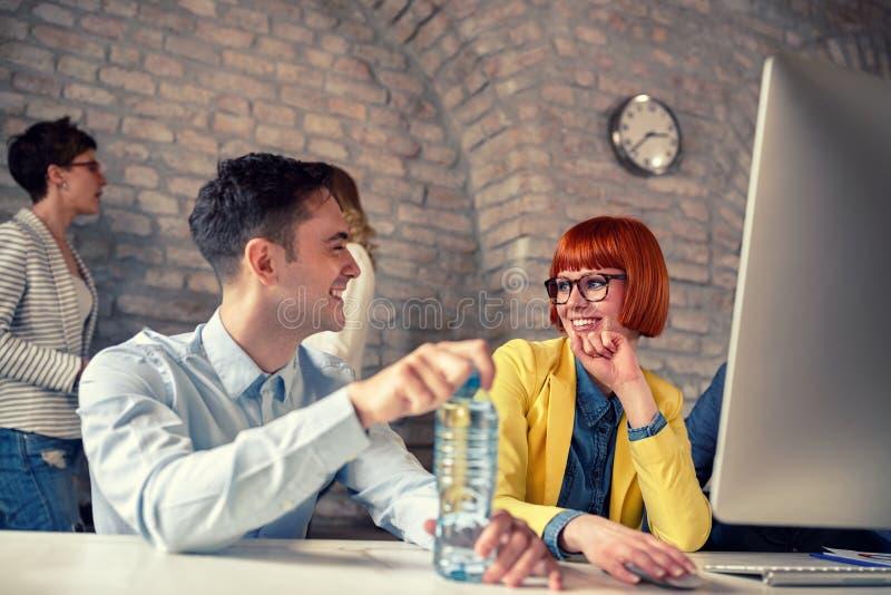 Δύο συνάδελφοι στην ευχάριστη συζήτηση στην αρχή στοκ φωτογραφία με δικαίωμα ελεύθερης χρήσης