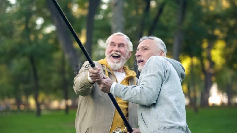 Δύο συνταξιούχοι που πιάνουν τα μεγάλα ψάρια, που τραβούν να περιστρέψει μαζί, υποστήριξη φιλίας στοκ φωτογραφία με δικαίωμα ελεύθερης χρήσης