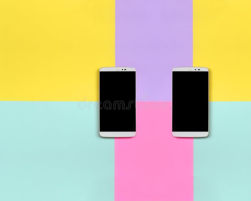 Δύο σύγχρονα smartphones με τις μαύρες οθόνες στο υπόβαθρο σύστασης του μπλε, κίτρινου, ιώδους και ρόδινου εγγράφου χρωμάτων κρητ στοκ φωτογραφία με δικαίωμα ελεύθερης χρήσης