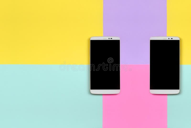 Δύο σύγχρονα smartphones με τις μαύρες οθόνες στο υπόβαθρο σύστασης του μπλε, κίτρινου, ιώδους και ρόδινου εγγράφου χρωμάτων κρητ στοκ φωτογραφίες με δικαίωμα ελεύθερης χρήσης