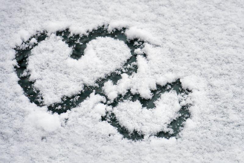 Δύο σύμβολα καρδιών που επισύρονται την προσοχή στο άσπρο χιόνι σε έναν ανεμοφράκτη αυτοκινήτων το χειμώνα στοκ εικόνα