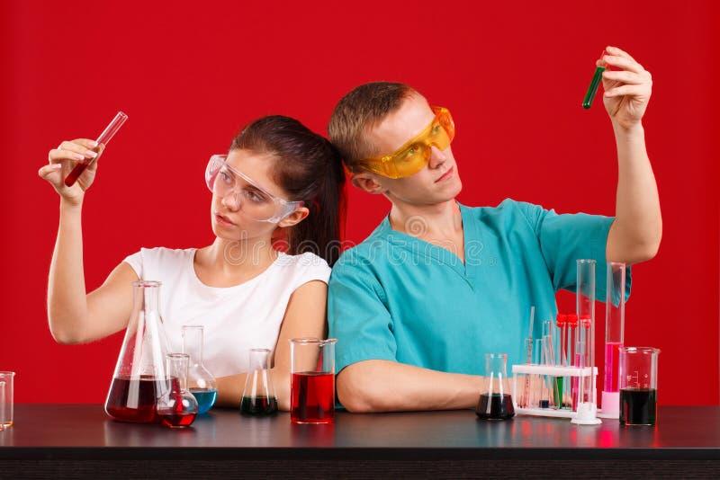 Δύο τεχνικοί εργαστηρίων, ένα κορίτσι και ένας τύπος, κρατούν τα μπουκάλια με ένα πολύχρωμο υγρό εξετάζοντας το Σε μια κόκκινη αν στοκ φωτογραφίες με δικαίωμα ελεύθερης χρήσης